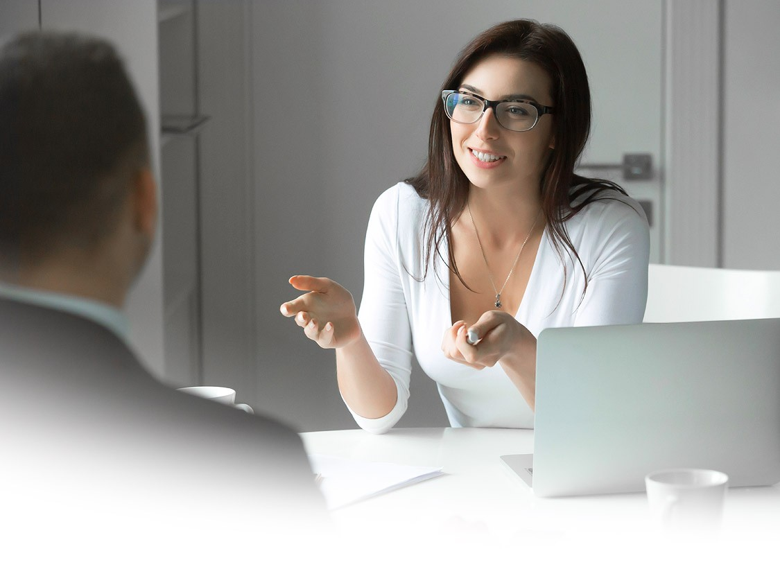 Business woman talks business support to a an at a desk